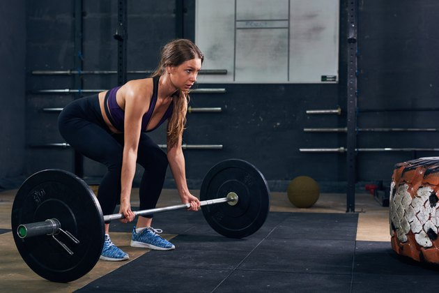 Woman Lifting Heavy Barbell in CrossFit Gym