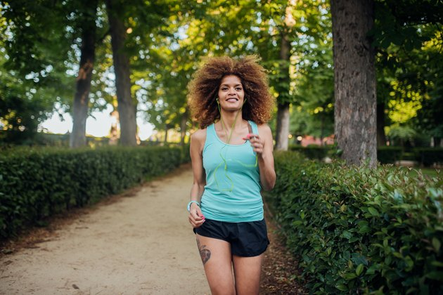 A woman jogging in a park surrounded by trees and bushes