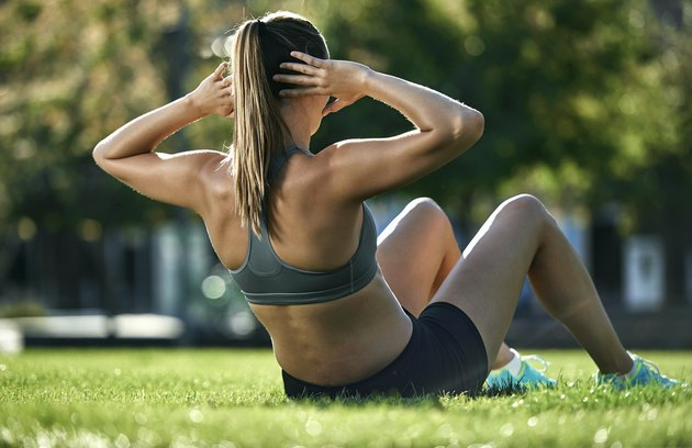 Young woman doing sit-ups in park