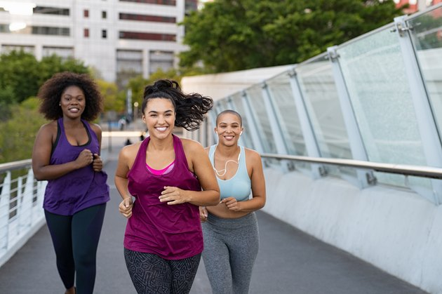 Three smiling women jogging together on a bridge