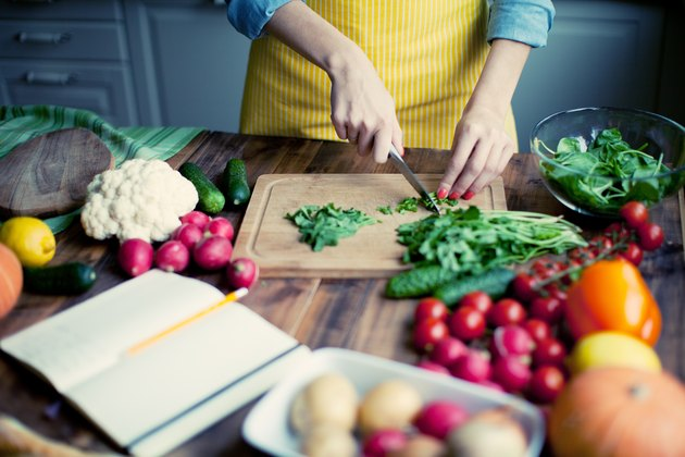 A woman in a yellow apron cutting up a variety of fresh vegetables in the kitchen