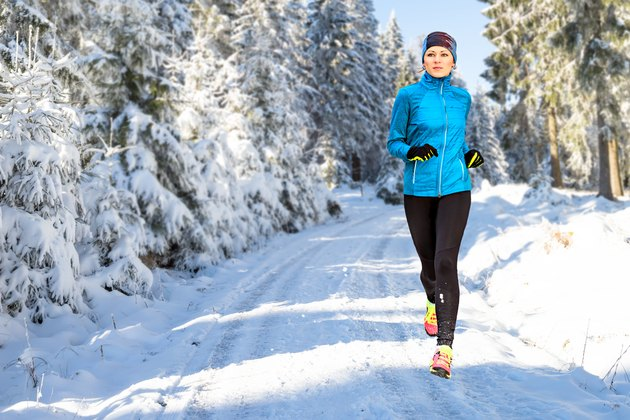 Young Woman Running On Snow Covered Road In Forest