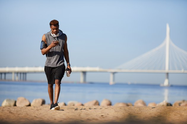 Serious black guy texting sms while walking over beach
