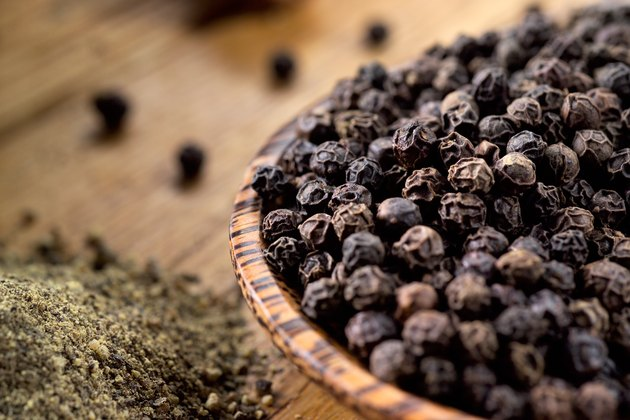 Close view of black peppercorns in a wooden bowl