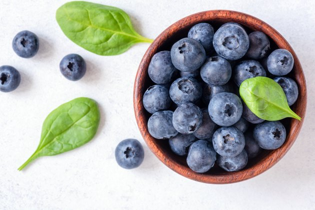 Fresh blueberries in bowl on white background, top view