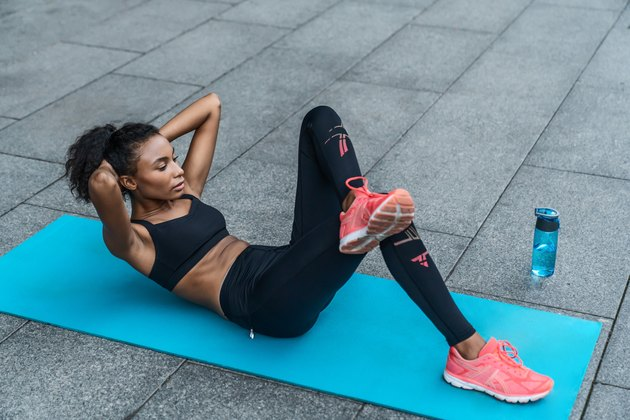 Young woman in sportswear doing abs workout on fitness mat