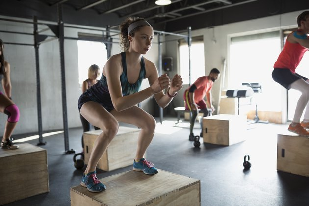 Focused woman jump squats in gym exercise class