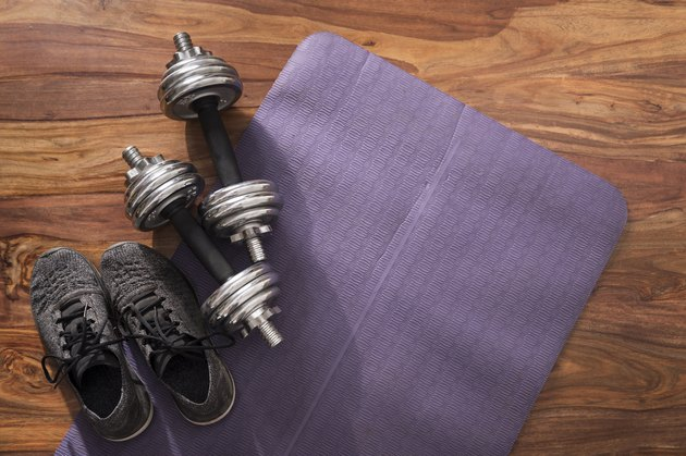 dumbbells and sneakers on an exercise mat