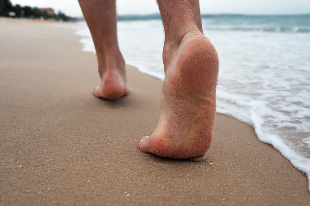 Close up of male feet and golden sand and ocean water. Summer activity and vacation holiday concept