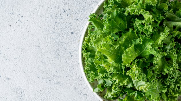 Kale leaves in bowl, copy space, top view
