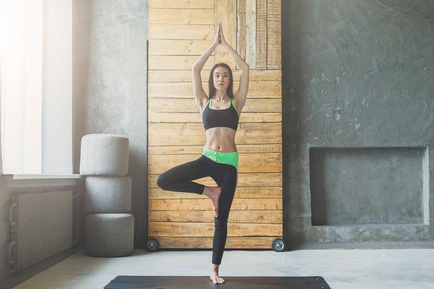 Young woman in yoga class, tree pose asana
