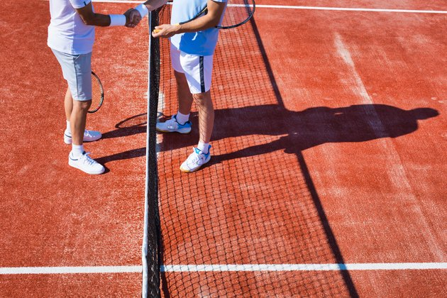 Men greeting while standing on tennis court during summer match