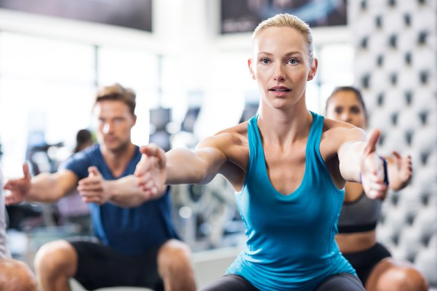 A woman doing squats in a workout class at the gym