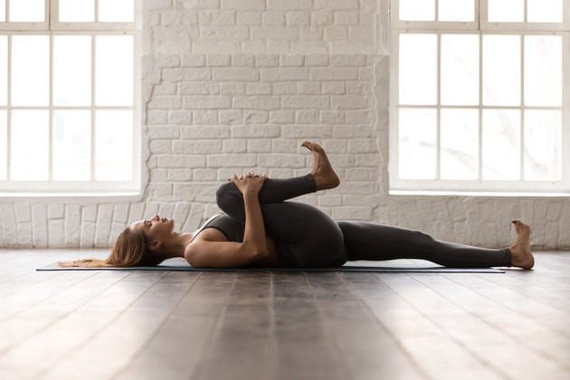 Woman practicing yoga, lying in Knees to Chest pose, Apanasana