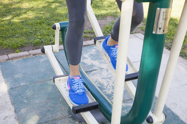 Cropped shot of womans legs training on step machine in park
