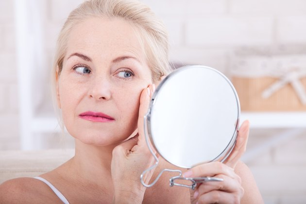 Forty years old woman looking at wrinkles in mirror. Plastic surgery and collagen injections. Makeup. Macro face. Selective focus