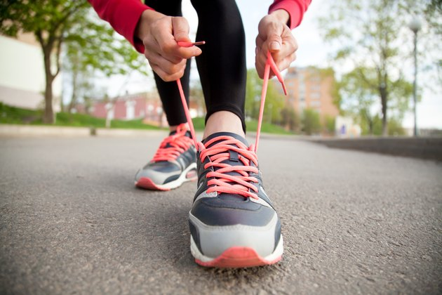 Female hands lacing running shoes. Closeup
