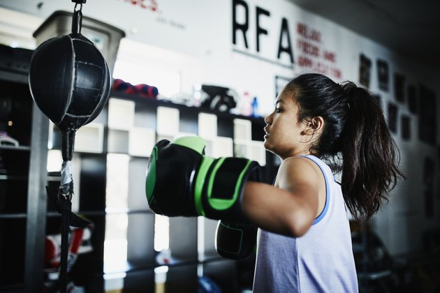 Young female boxer working on double ended bag in boxing gym