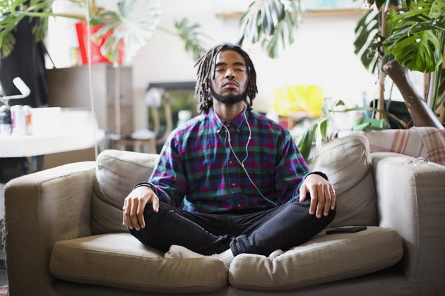 Man Sitting on His Couch While Doing Exercises to Increase Alpha Brain Waves