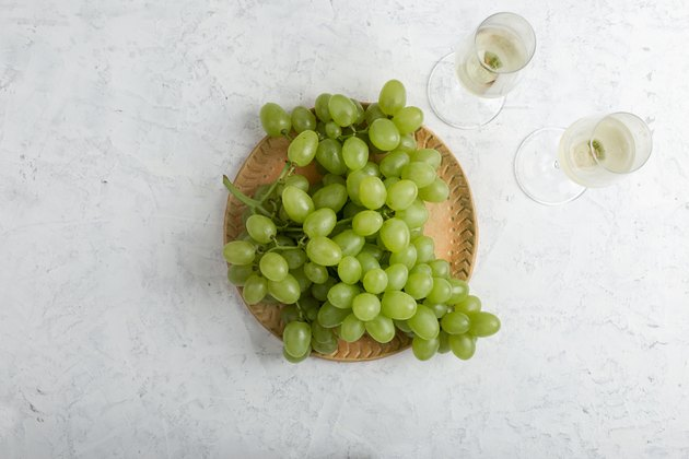Bunch of ripe green grapes and  two glasses of white wine
