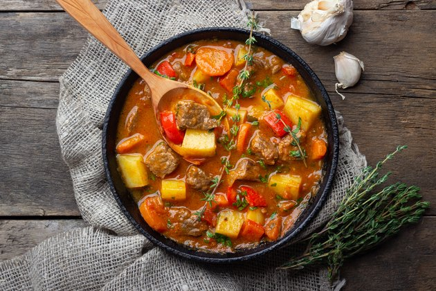 Goulash, beef stew or bogrash soup with meat, vegetables and spices in cast iron pan on wooden table.