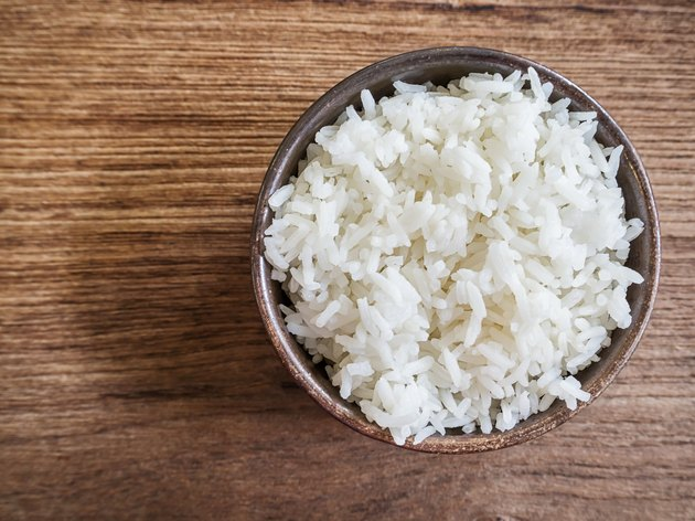 Cooked jasmine rice in a bowl on wooden table