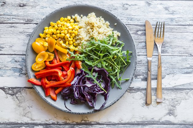 Glass of rainbow salad with bulgur, rocket and different vegetables and bowls with ingredients