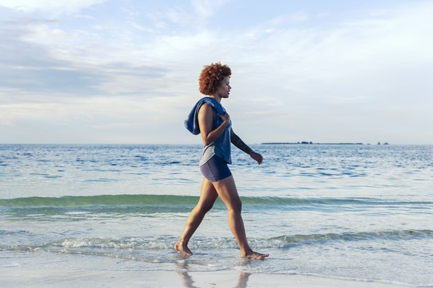 young female walks along beach
