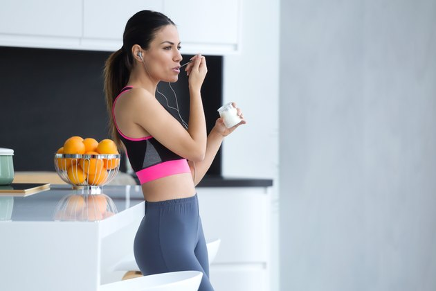 Sporty young woman listening to music with mobile phone while eating yogurt in the kitchen at home.