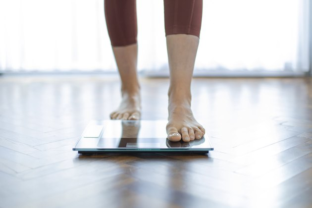 Young woman on home scales