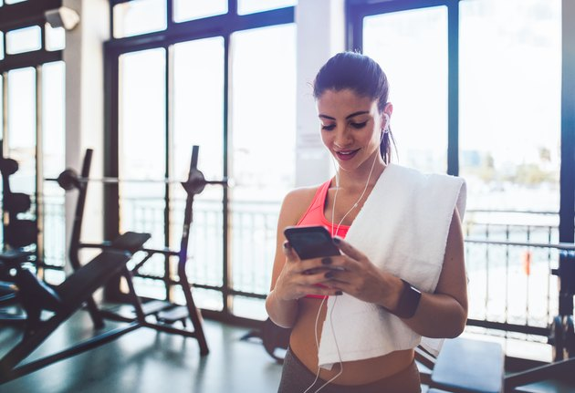 Woman using fitness application with smartwatch and smartphone at gym