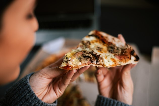 Eating pizza at night. Close-up