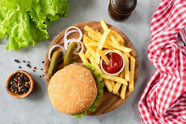 Burger with sesame, fries, pickles and lettuce salad