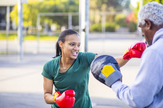 Young woman practicing boxing for health benefits outside with older man