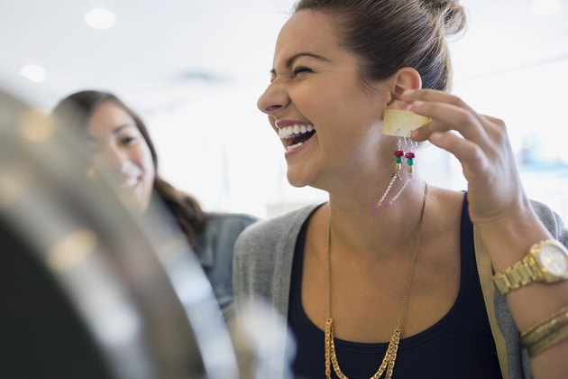 Laughing woman holding earrings in shop