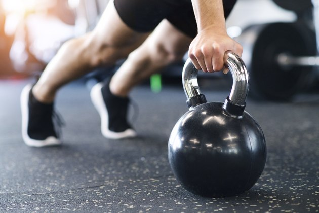 man in gym doing push-ups in a kettlebell workout