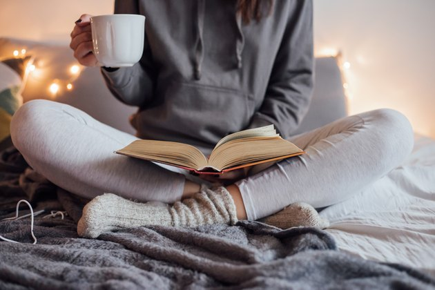 Girl drinking hot tea and reading book in bed