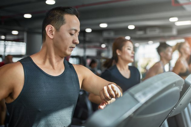 Man using smart watch and treadmill in gym