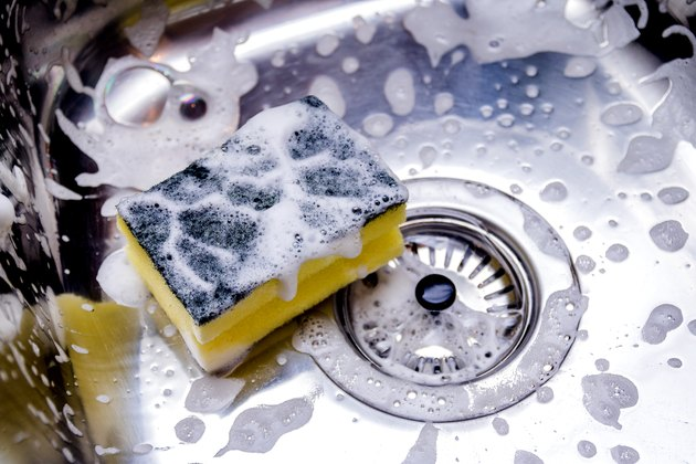 Close view of a sponge full of soap in a kitchen sink
