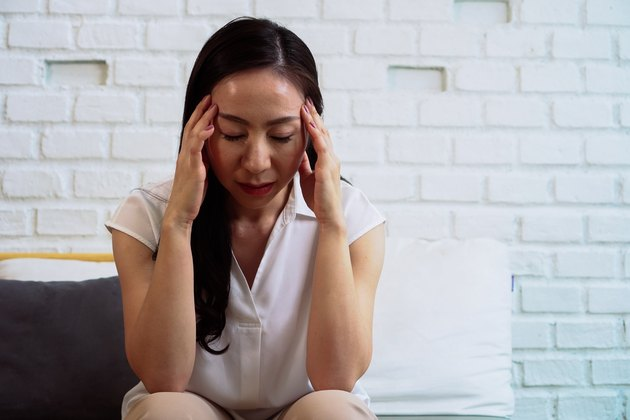 Beautiful stressed woman sitting with closed eyes and hands on head and suffering from headache at home