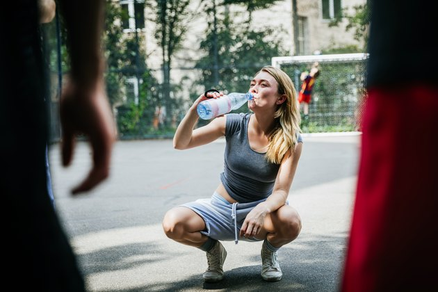 Young Woman Taking Break From Basketball Game To Drink Water