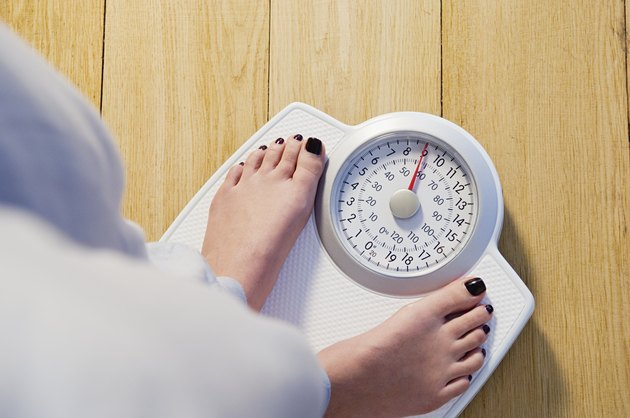 Woman standing on weight scales