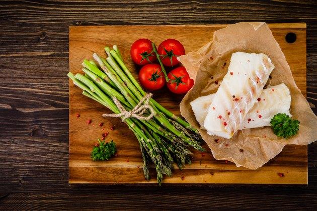 Fresh raw cod fillets on cutting board
