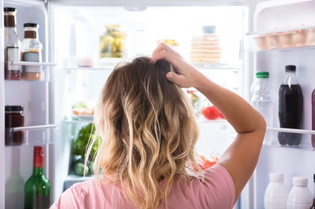 Confused woman with no appetite looking into refrigerator at home