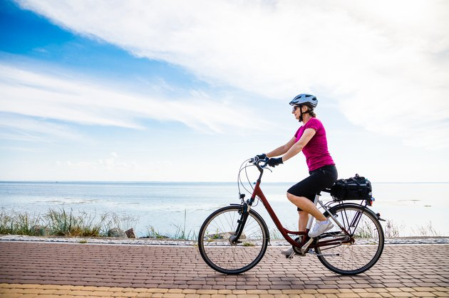 Woman riding bike at seaside