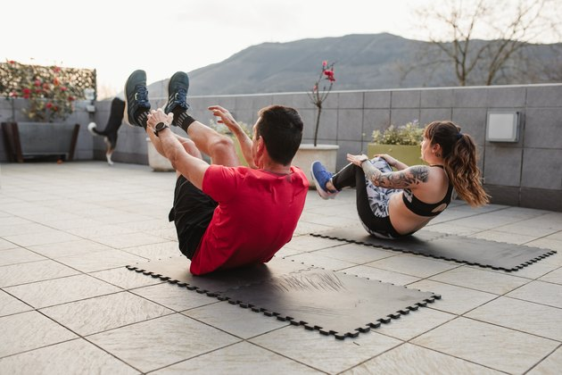 mature man and young woman Doing crunches with sportswear on the terrace of his house at sunset