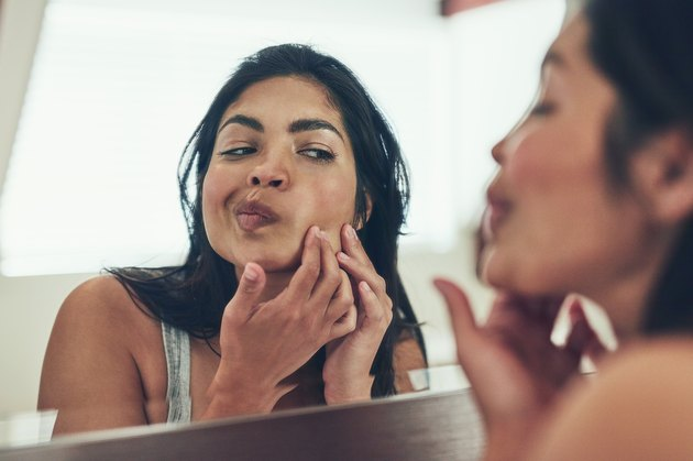 A woman looking at her skin in the mirror after a workout