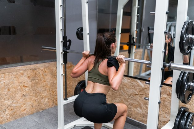 Female Athlete Doing Squats With Weights In Gym
