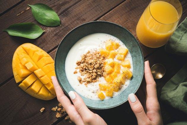 Bowl of yogurt with mango and granola for breakfast