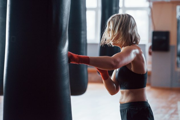 Full kickback. Female boxer is punching the bag. Blonde have exercise in the gym